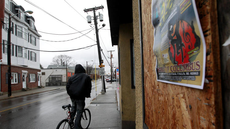 In this Thursday, Jan. 12, 2012 photo, a cyclist rides past boarded-up windows on a building in Central Falls, R.I. The state of Rhode Island stepped in to take over financially struggling Central Falls in 2010, with a state-appointed receiver filing for bankruptcy on behalf of the city in August 2011. (AP Photo/Steven Senne)