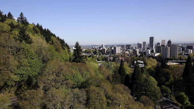 In this Wednesday, April 24, 2013 photo, the forested hills west of downtown Portland, Ore., shown here are honeycombed with miles and miles of hiking trails.  One of the latest Portland  efforts is something called the 4T trail, a tour that incorporates the city's light-rail trains, trolleys, forest trails and even a sky tram that gives spectacular views of downtown and the surrounding countryside from the West Hills. (AP Photo/Don Ryan)