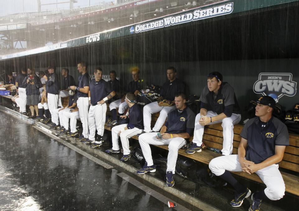 Kent State players wait in the dugout as heavy rain drenches pregame warmups before an NCAA College World Series elimination baseball game against South Carolina in Omaha, Neb., Wednesday, June 20, 2012. (AP Photo/Nati Harnik)