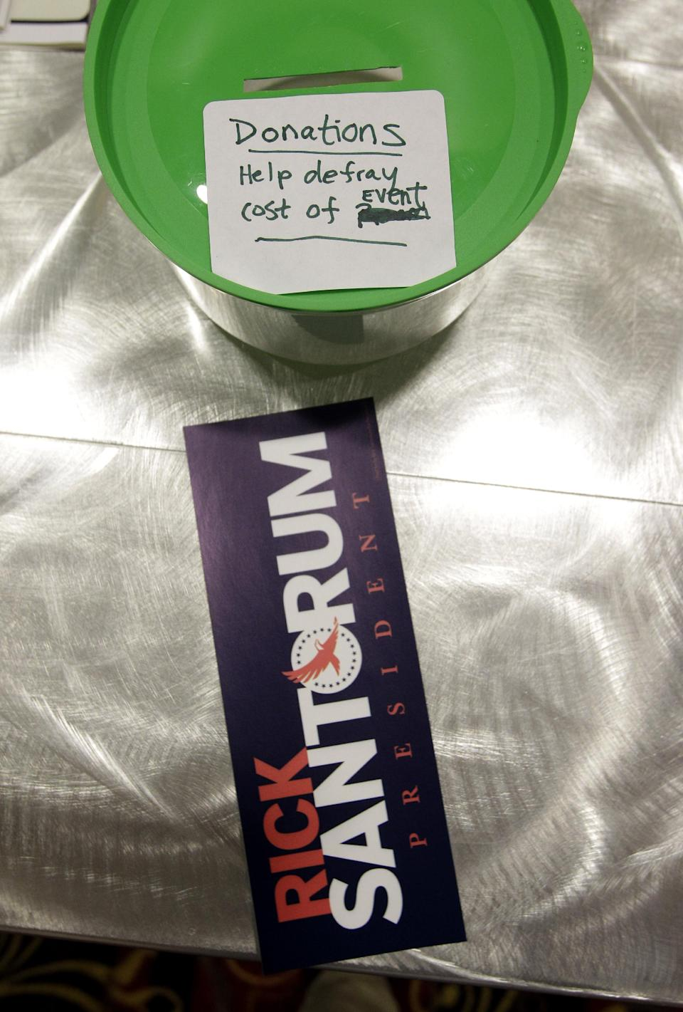 A donation bucket and bumper sticker are seen a Tea Party rally for Republican presidential candidate, former Pennsylvania Sen. Rick Santorum, Saturday, Feb. 18, 2012, in Columbus, Ohio.  (AP Photo/Eric Gay)
