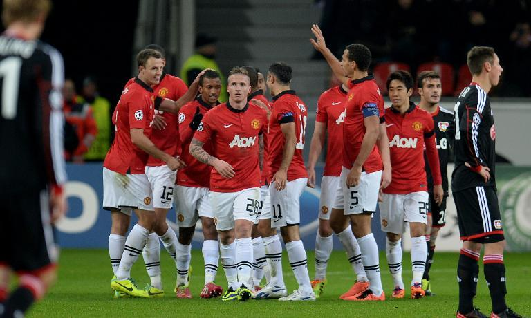 Manchester United players celebrate scoring a goal during their UEFA Champions League Group A match against Bayern Leverkusen, in Leverkusen, western Germany, on November 27, 2013