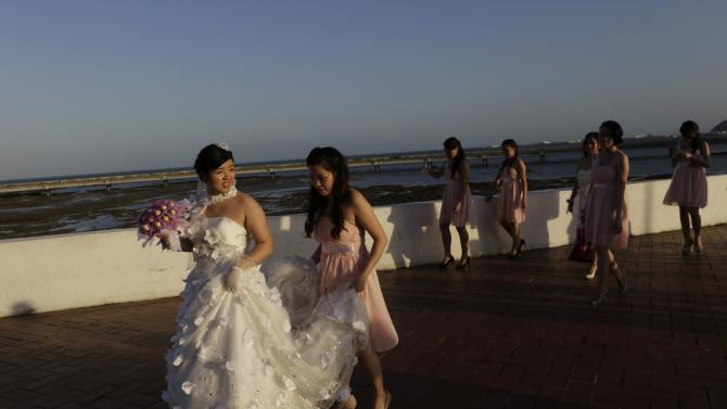 Araseli walks along the seafront with her bridesmaids during a photographic session on her wedding day in Panama City