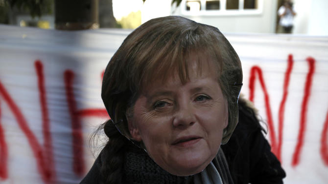 A protestor with a mask of German Chancellor Angela Merkel shout slogans during a protest outside of the parliament in capital Nicosia, Cyprus, Monday, March 18, 2013. A vote on a bailout package for Cyprus that includes an immediate tax on all savings accounts has been postponed until Tuesday evening. Yiannakis Omirou, the speaker of Parliament, said the delay was needed to give the government time to amend the deal reached over the weekend that prompted an outcry from those who thought their money was safe. In order to get euro 10 billion ($13 billion) in bailout loans from international creditors, Cyprus agreed to take a percentage of all deposits — including ordinary citizens' savings — an unprecedented step in Europe's over 3 year debt crisis. (AP Photo/Petros Karadjias)