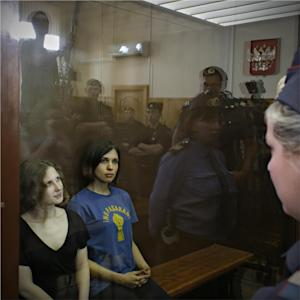 "Feminist punk group Pussy Riot members, from left, Maria Alekhina and Nadezhda Tolokonnikova sit in a glass cage at a court room in Moscow, Russia on Friday, Aug. 17, 2012. A judge found three members of the provocative punk band Pussy Riot guilty of hooliganism on Friday, in a case that has drawn widespread international condemnation as an emblem of Russia's intolerance of dissent. T-shirt on right worn by Tolokonnikova is Spanish and translates to ""They shall not pass"", a slogan often used to express determination to defend a position against an enemy. (AP Photo/Sergey Ponomarev)"