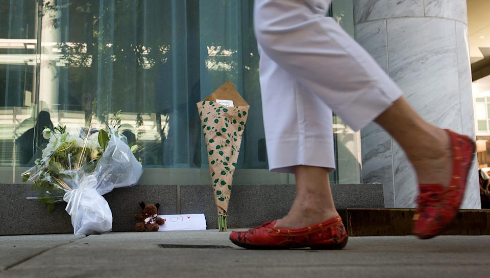 A woman walks past a small memorial Sunday, July 14, 2013, for Canadian actor Cory Monteith outside the Fairmont Pacific Rim Hotel where he died on Saturday, in Vancouver, British Columbia. Monteith's body was found in a room at the hotel Saturday. (AP Photo/The Canadian Press, Darryl Dyck)