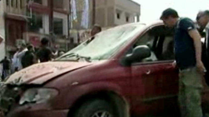 In this image made from pool video provided by APTN, Libyan men inspect the damages of a vehicle at the scene of a car bomb explosion in Benghazi, Libya, Monday, May 13, 2013. A car bomb exploded Monday near a hospital in the eastern Libyan city of Benghazi, killing many, officials said, in one of the biggest attacks since the end of the civil war that ousted former dictator Moammar Gadhafi. (AP Photo/APTN, Al Ahrar)