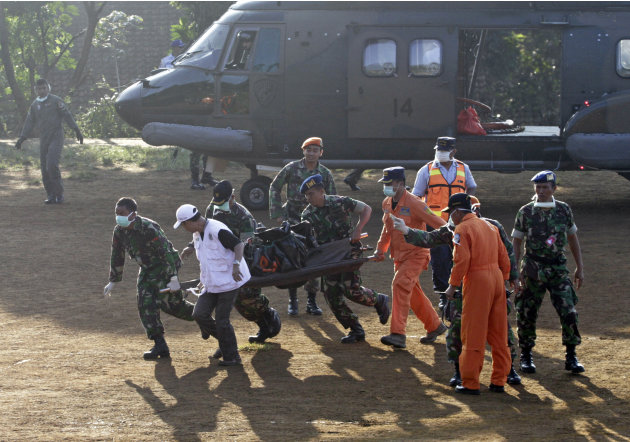 Indonesian soldiers carry a victim of  Wednesday's plane crash at Cijeruk in Bogor, West Java, Indonesia, Saturday, May 12, 2012.  Search teams who scaled a volcano's steep slopes found at least 12 bo