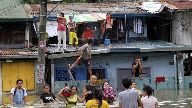 Residents wade through floodwaters on a street while others watch from the rooftop of their house after Tropical Storm Fung-Wong battered Cainta, Rizal province