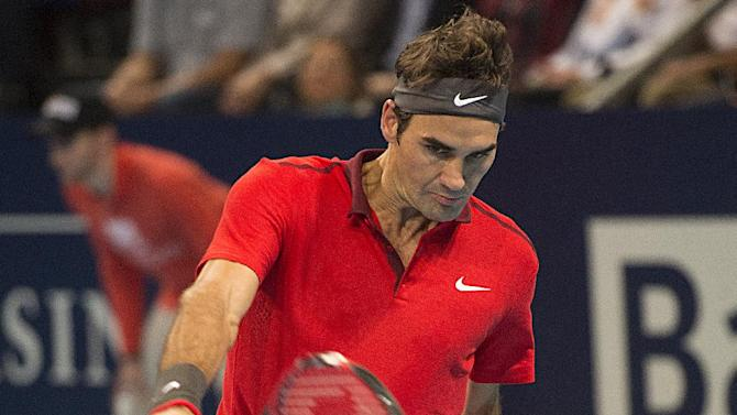 Switzerland's Roger Federer returns a ball to Uzbekistan's Denis Istomin during their round of sixteen match at the Swiss Indoor tennis tournament at the St. Jakobshalle in Basel, Switzerland, on Thursday, Oct. 23, 2014. (AP Photo/Keystone, Georgios Kefalas)