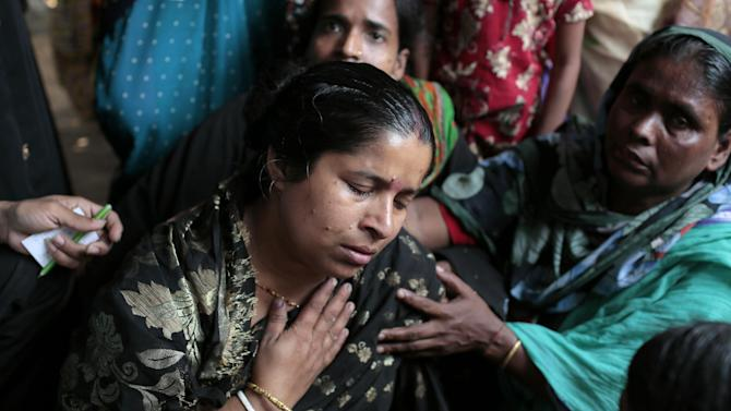 A Bangladeshi Hindu devotee Dipali Das cries as she sits next to the body of a relative who was killed in a stampede during a Hindu bathing ritual in Langalbandh, 20 kilometers (12 miles) southeast of capital Dhaka, Bangladesh, Friday, March 27, 2015. Local police chief Nazrul Islam said the stampede took place in a Hindu pilgrimage spot on the banks of the Brahmaputra river during an annual religious bathing ritual. (AP Photo/ A.M. Ahad)