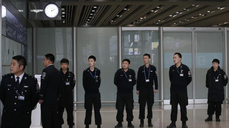 Security personnel are seen at the Beijing Capital International Airport after Malaysia Airlines flight MH370 went missing, in Beijing