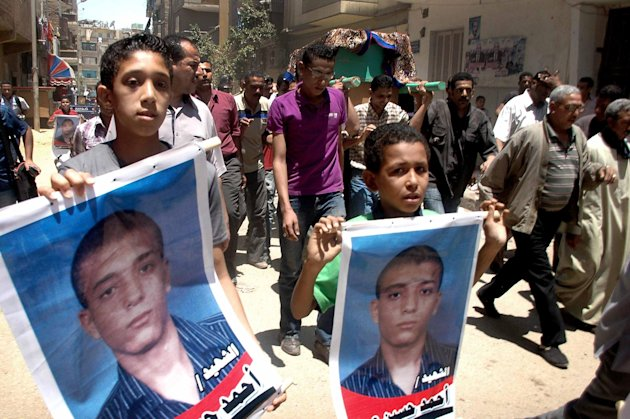 Egyptian boys hold posters of Ahmed Hussein Eid who was fatally stabbed by three bearded men during his funeral procession in the city of Suez, Egypt, Wednesday, July 4, 2012. The murder of a university student by suspected militants as his girlfriend looked on is fueling fears in Egypt that vigilante groups seeking to enforce a strict interpretation of Islams teachings may be feeling confident with an Islamist president in office to take over the streets. (AP Photo)