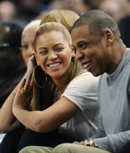 FILE - In this Feb. 20, 2012 file photo, entertainer Jay-Z reacts with his wife, Beyonce, during the third quarter of an NBA basketball game between the New York Knicks and New Jersey Nets, at Madison Square Garden in New York. Beyonce will battle her husband for video of the year at the BET Awards, and now both performers are confirmed to attend, The Associated Press reports Friday, June 29, 2012. Beyonce is the second most nominated act. She&#39;s up for six awards. Jay-Z is nominated for five. (AP Photo/Bill Kostroun, File)