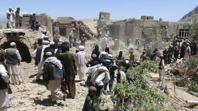 FILE - In this Wednesday, June 6, 2012 file photo, Afghan villagers gather near a house destroyed in an apparent NATO raid in Logar province, south of Kabul, Afghanistan. The number of U.S. drone strikes in Afghanistan jumped 72 percent in 2012, killing at least 16 civilians in a sharp increase from the previous year, the U.N. said Tuesday in a sign of the changing mission as international forces prepare to withdraw combat forces in less than two years. (AP Photo/Ihsanullah Majroh, File)