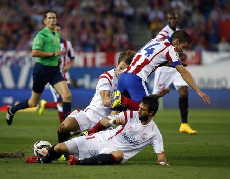 Atletico Madrid's Gabi fights for the ball with Sevilla's Krychowiak and Pareja during their Spanish first division soccer match in Madrid
