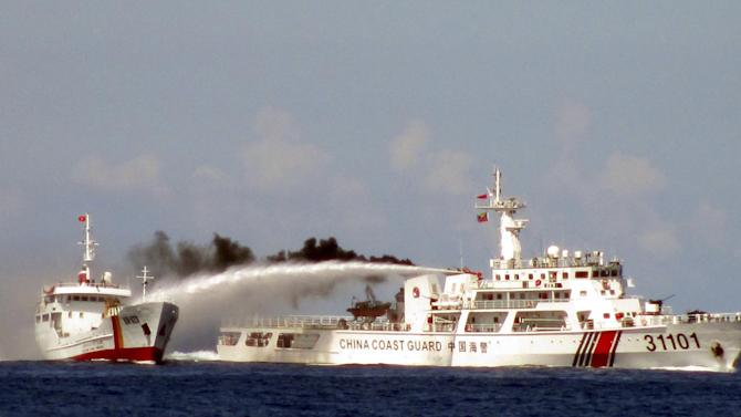 In this Sunday, May 4, 2014 file image made from video released by Vietnam Coast Guard, a Chinese coast guard vessel, right, fires water cannon at a Vietnamese vessel off the coast of Vietnam after China deployed an oil rig in disputed South China Sea waters. A top Chinese diplomat will visit Vietnam this week after China's deployment of a giant oil rig off Vietnam's coast in May increased tensions. (AP Photo/Vietnam Coast Guard, File)