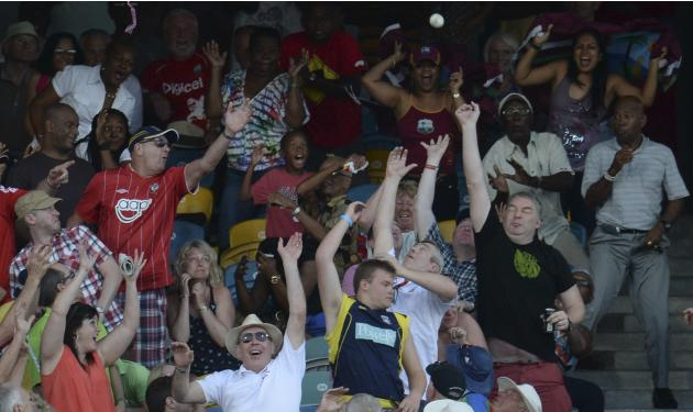 Spectators attempt to catch a six during the second T20 international cricket match between England and the West Indies in Barbados