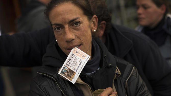 """A woman reacts to the camera while she bites a ticket of the famed Christmas lottery, in Madrid, Friday, Dec. 21, 2012.  Known as """"El Gordo"""" (The Fat One) and billed as the world's richest lottery, the drawing will hand out about 2.5 billion of euros (US dlrs 3.3 billion) on upcoming Saturday. The top prize is about 400,000 euros ($530,000) but there are expected to be hundreds or thousands of tickets awarded for that amount. (AP Photo/Daniel Ochoa de Olza)"""
