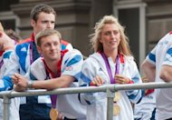 British gold medal winning cyclists Jason Kenny and Laura Trott look down from their float during a parade celebrating athletes who competed in the London 2012 Olympic and Paralympic Games in London. Huge crowds cheered Britain&#39;s Olympic and Paraylmpic athletes during a victory parade to Buckingham Palace amid hopes that the golden sporting summer will give the country a long-term boost