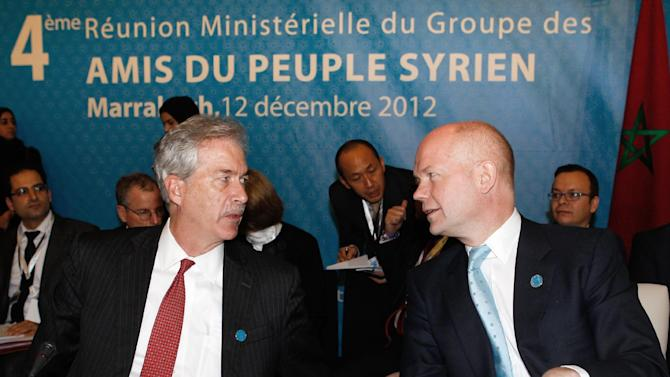 """U.S. Deputy Secretary of State William J. Burns, left, chats with Britain's Foreign Minister William Hague at a meeting of the Friends of the Syrian People in Marrakech, Morocco, Wednesday Dec. 12, 2012. The Syrian opposition called for """"real support"""" and not just recognition on Wednesday, hours after the U.S. declared its new coalition was the """"legitimate representative"""" of its country's people. Banner behind reads: 4th meeting of the group of """"Friends of the Syrian People"""". (AP Photo/Abdeljalil Bounhar)"""