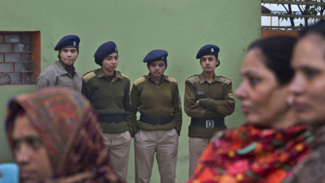 Female Indian paramilitary soldiers watch as Indian women march to mourn the death of a gang rape victim in New Delhi, India, Wednesday, Jan. 2, 2013. India's top court said it will decide whether to suspend lawmakers facing sexual assault charges as thousands of women gathered at the memorial to independence leader Mohandas K. Gandhi to demand stronger protection for their safety. (AP Photo/ Dar Yasin)