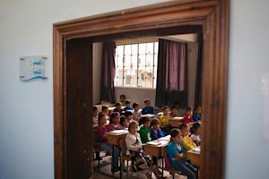 Syrian children attend a class at a school in the Saif …