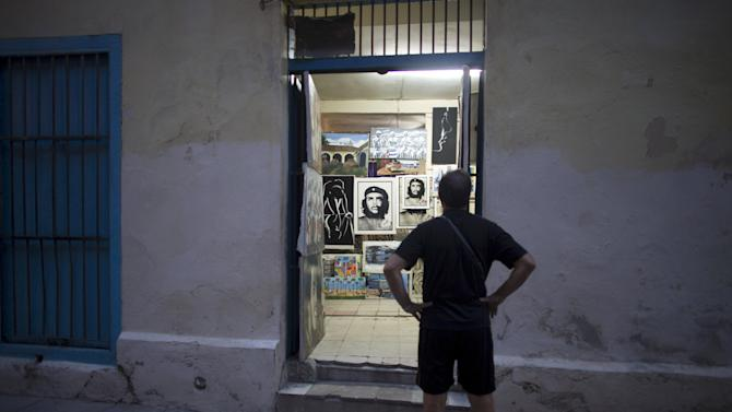 A tourist looks at images displayed in a shop in downtown Havana