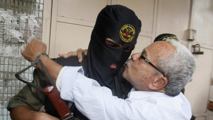 A Gaza man hugs a Palestinian Islamic Jihad militant after a press conference in Gaza City, Thursday, Nov. 22, 2012.  Gazans are celebrating a cease-fire agreement reached with Israel to end eight days of the fiercest fighting in nearly four years constricting the Gaza Strip. (AP Photo/Hatem Moussa)