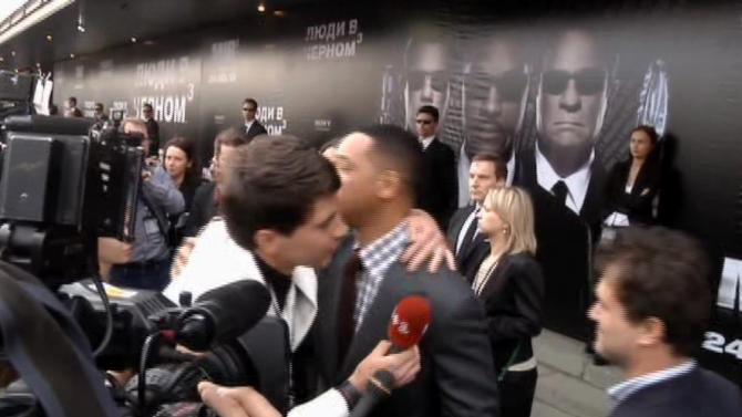 """FILE - In this video image taken from AP video on May 18, 2012, U.S. actor Will Smith, center right, is embraced by reporter Vitalii Sediuk, white suit, from the Ukrainian television channel 1+1 on the red carpet before the premiere of """"Men in Black III"""" in Moscow. Smith later slapped Sediuk who tried to kiss him before the Moscow premiere. Sediuk's antics have left him with fewer friends in the entertainment world after his publicist and television station cut ties with him over pranks that have once again landed the 25-year-old in handcuffs. He's kissed Will Smith in Moscow, tried to steal Adele's spotlight at the Grammys, dove under America Ferrera's dress at Cannes and now accosted Brad Pitt on the red carpet of a Hollywood premiere. (AP Photo via AP video, File)"""