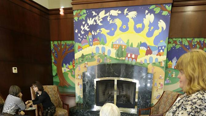 In this Tuesday, Jan. 8, 2013 photo, caregiver Kim Bauer, right, pauses as the elderly woman she is helping looks at a decorative fireplace at Cedar Village retirement community, in Mason, Ohio. The woman she is helping has suffered abuse by a relative. The Shalom Center that is a part of the community helps the woman by offering shelter, along with medical, psychological and legal help, to elderly abuse victims in this northern Cincinnati suburb. The center asked that her identity be protected for this story because the close relatives who allegedly abused her don't know where she is. (AP Photo/Al Behrman)