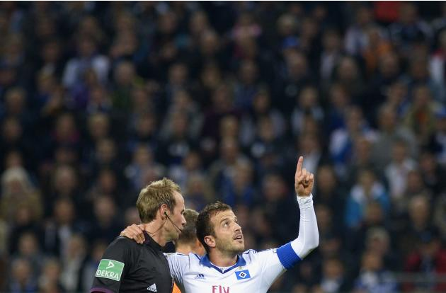 Hamburger SV's van der Vaart embraces referee Stegemann as he gestures during second round German soccer cup match against Greuther Fuerth in Hamburg