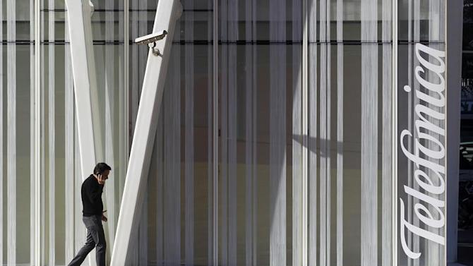 A man speaks by a mobile next to Telefonica's tower in Barcelona