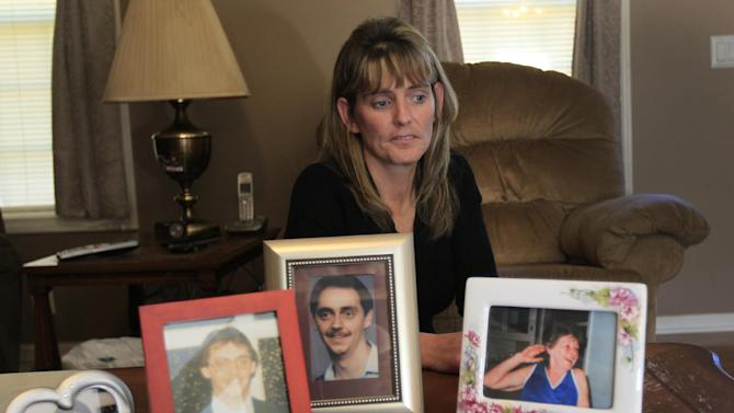 In this Oct. 17, 2012 photo, Jody Robinson, the younger sister of James Cotaling, who was murdered in 1990, sits next to photos of him, left three, as she describes his personality at her home in Davisburg, Mich. Robinson is very outspoken against reconsidering the sentences of juvenile offenders serving life without parole. Her views are shaped by her family's own heartbreak and anger at the loss of Cotaling. Barbara Hernandez, one of the two people convicted in his murder, was 16 at the time. (AP Photo/Carlos Osorio)