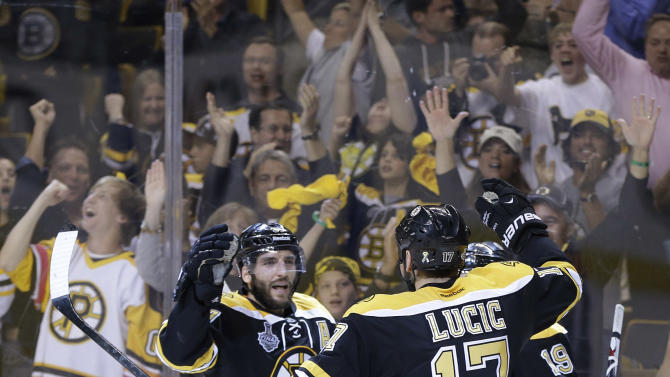 Boston Bruins center Patrice Bergeron, left, celebrates his goal against the Chicago Blackhawks with Milan Lucic (17) and Tyler Seguin (19) during the second period in Game 3 of the NHL hockey Stanley Cup Finals in Boston, Monday, June 17, 2013. (AP Photo/Elise Amendola)