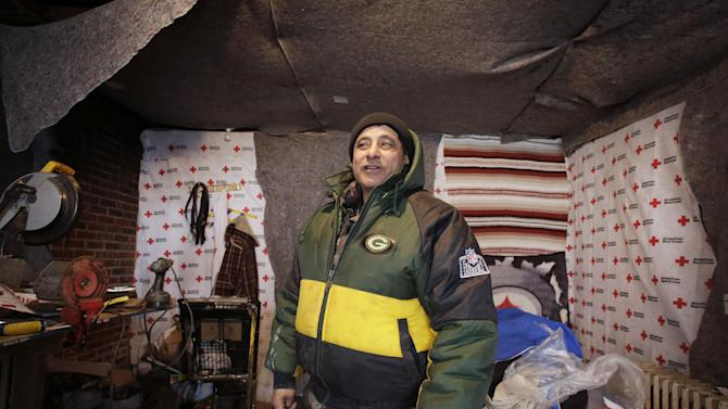 FILE - In this file photo of Jan. 23, 2013, Eddie Saman shows how he insulated his home with blankets donated by the Red Cross, in the Staten Island borough of New York. The house was badly damaged by Superstorm Sandy and will have to be renovated. Three months after Sandy struck, thousands of storm victims in New York and New Jersey are stuck in limbo. Waiting for the heat to come on, for insurance money to come through, for loans to be approved. Waiting, in a broader sense, for their upended lives to get back to normal. (AP Photo/Mark Lennihan, File)