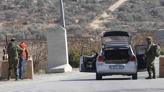 An Israeli soldier searches a Palestinian man before allowing him to pass through the Israeli Beit Forik military checkpoint near the West Bank city of Nablus