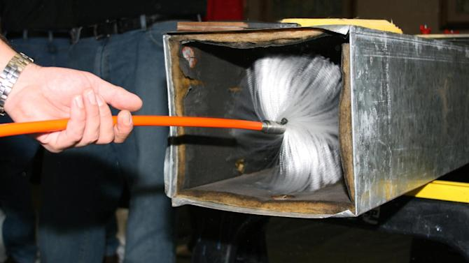 This undated publicity photo provided by NADCA shows  a technician using a brush to clean ductwork. If you want to freshen up the air in your home and make your heating and cooling systems work more efficiently, you might consider having the ductwork cleaned. (AP Photo/NADCA)