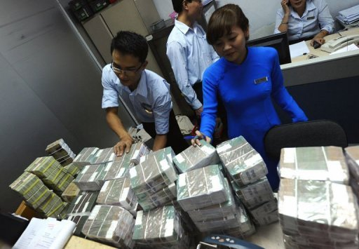 <p>Employees of a local Asia Commercial Bank (ACB) outlet arrange bricks of dong bank notes sent in from the state bank in Hanoi on August 23, 2012. Vietnam's stock markets have lost nearly $4.0 billion in value after two top bankers were arrested this week in a widening police probe into the banking sector, state media said Friday.</p>