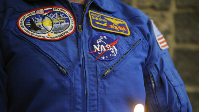 """Five-time shuttle astronaut Robert """"Hoot"""" Gibson stands near a candle honoring fallen astronauts during a remembrance ceremony honoring astronauts killed in three accidents plus 40 others who were part of the astronaut corps and have died, Thursday, Jan. 29, 2015, at Marshall Space Flight Center in Huntsville, Ala.  (AP Photo/Jay Reeves)"""