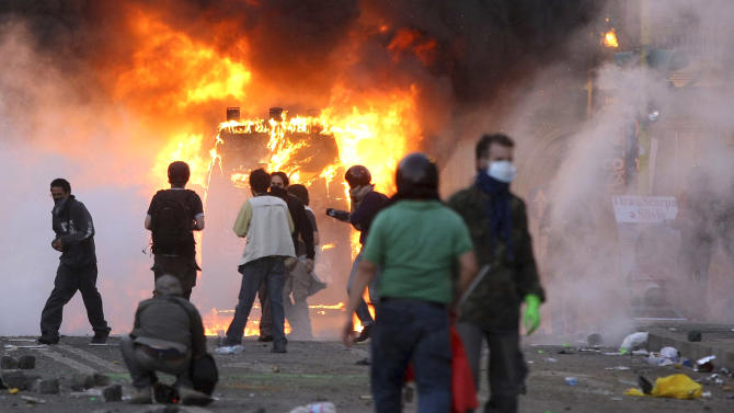 """A Carabinieri (Italian paramilitary police) van is engulfed in flames after protesters set it on fire during clashes in Rome, Saturday, Oct. 15, 2011. Italian police fired tear gas and water cannons as protesters in Rome turned a demonstration against corporate greed into a riot Saturday, smashing shop and bank windows, torching cars and hurling bottles. The protest in the Italian capital was part of """"Occupy Wall Street"""" demonstrations against capitalism and austerity measures that went global Saturday, leading to dozens of marches and protests worldwide. (AP Photo/Roberto Monaldo, Lapresse)   Italy Out"""