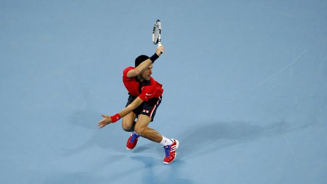 Novak Djokovic of Serbia hits a return against John Isner of U.S. during their men's singles match at the China Open tennis tournament in Beijing