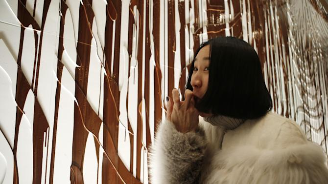 Lucky Magazine editor-in-chief Eva Chen tastes chocolate syrup that was dripped down a wall during the presentation of the Fall 2014 Opening Ceremony show at Fashion Week, Sunday, Feb. 9, 2014, in New York. (AP Photo/Kathy Willens)