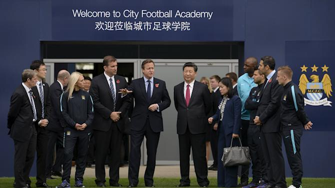 File photo of Britain's Prime Minister Cameron standing with China's President Xi and Manchester City Chairman Mubarak during a visit to the City Football Academy in Manchester