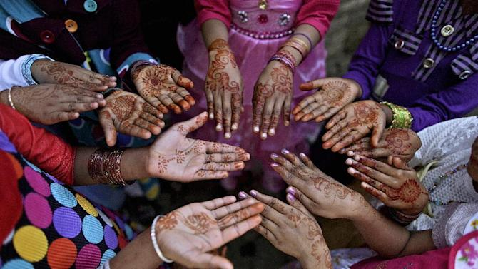 AP10ThingsToSee - Pakistani Christian girls display their hands decorated with Bangles and painted with Henna paste as they celebrate Easter  following a mass in a Christian neighborhood in Islamabad, Pakistan, Sunday, March 31, 2013. (AP Photo/Muhammed Muheisen, File)