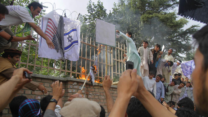 Afghans burn U.S. and Israeli flags in Kabul, Afghanistan, Sunday, Sept. 16, 2012 during a protest against an Internet video that mocks the Prophet Muhammad. The video sparked protests throughout the Muslim world and Afghan government blocked the YouTube site that hosts the video and its parent company, Google Inc., over the weekend in a move to prevent violent protests. (AP Photo/Ahmad Jamshid)