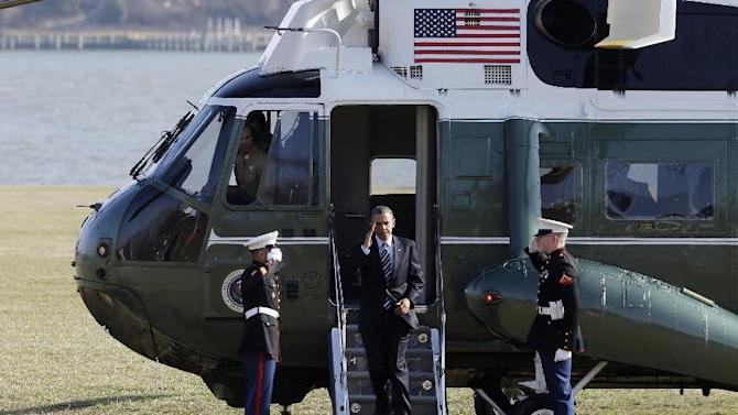 President Barack Obama returns a salute as he walks from Marine One helicopter as he lands at the U.S. Naval Academy before attending the Senate Democratic Issues Conference in Annapolis, Md., Wednesday, Feb. 6, 2013. (AP Photo/Charles Dharapak)