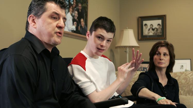 FILE - In this May 14, 2008, file photo, Steven Domalewski, center, sits with his parents Joseph and Nancy Domalewski during an interview at their home in Wayne, N.J. Domalewski, left brain-damaged after being struck by a line drive while he was playing in a youth baseball game, will receive $14.5 million to settle his lawsuit against the bat manufacturer, Little League Baseball and a sporting goods chain. The settlement of was announced in state Superior Court on Wednesday morning, Aug. 22, 2012, in Passaic County. (AP Photo/Mike Derer)