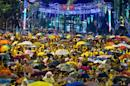 Protestors take shelter under umbrellas during a rain-shower on the second day of the anti-government rally in Kuala Lumpur on August 30, 2015