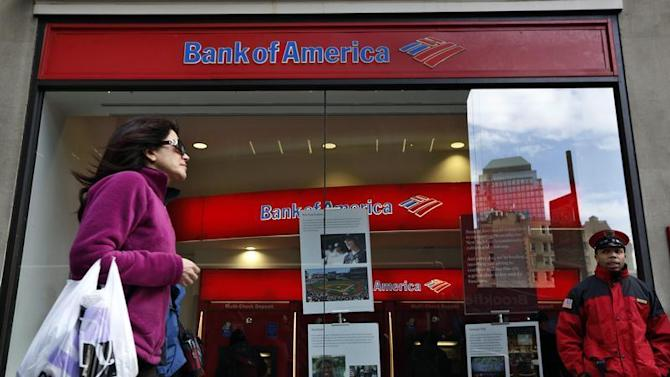 A woman walks past as customers use ATMs at a Bank of America banking center in New York's financial district