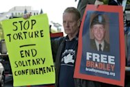 "A man holds up posters in support of Bradley Manning, accused of leaking a trove of secret documents to Wikileaks. Manning challenged US prosecutors Wednesday to prove he intended to ""aid the enemy"" by turning over documents to the whistleblower website, arguing that spilling secrets could not be treated as a plot to help Al-Qaeda"